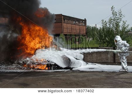 firefighter  quenches burning tires