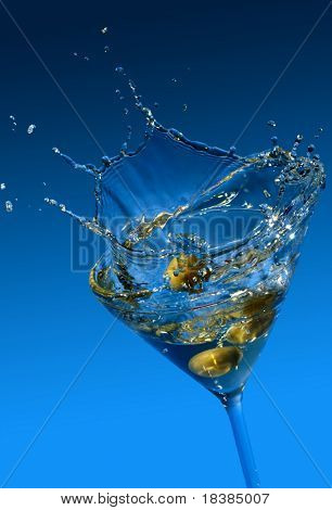 olive splashing in a cocktail glass