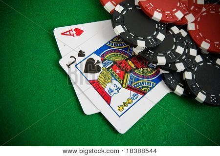Ace of hearts and black jack with red and black poker chips in the background.