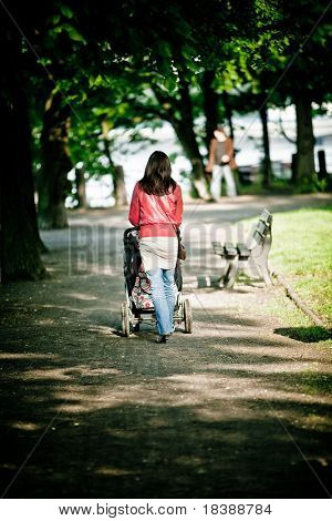 Woman walking with baby carriage in park