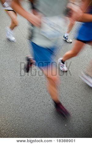 Man running in city marathon - motion blur