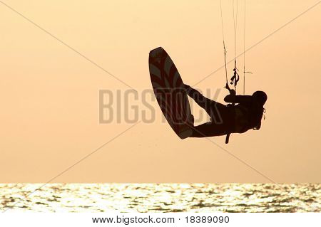 Kitesurfer jumps over the water during training day on Mediterranean sea.