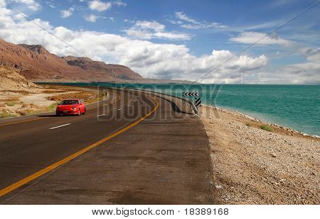 Rotes Auto auf einer Autobahn, die entlang des Toten Meeres von einer Seite und Edom Berge bei Arava-Wüste f