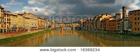 Panoramic view on old houses, Arno river and Ponte Vecchio at evening in Florence, Italy.