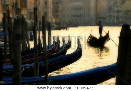 Gondola passing by gondolas parking on Grand Canal at sunset time in Venice, Italy.