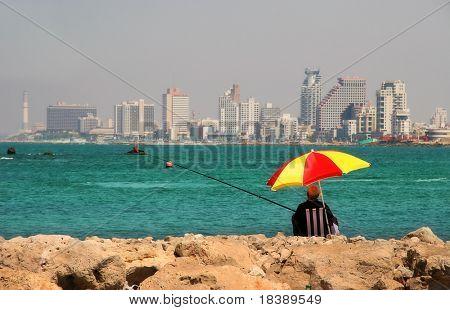 Fisherman sitting on wave breaker on Mediterranean Sea and looking at the modern building of Tel-Aviv, Israel..
