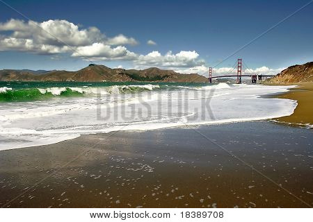 Ocean waves on Baker Beach and Golden Gate Bridge on background in San Francisco, USA.