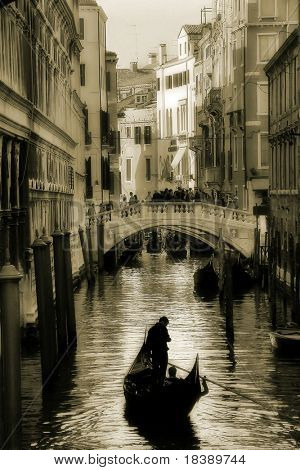 Small canal and gondola among the houses in Venice, Italy (sepia toned).