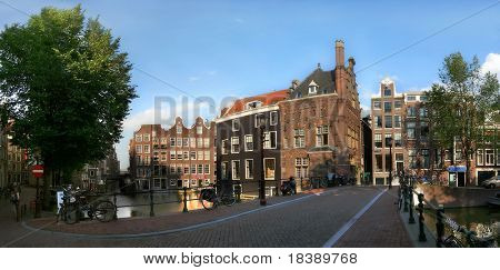 Panoramic view on bridge over the canal (Amstel river) and old buildings on water in the historic part of Amsterdam, Netherlands.