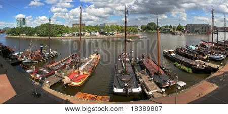 Panoramic view on Amstel river and pier with ships and boats in Amsterdam, Netherlands.