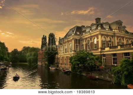 Small boat  passing by old historic house in Amsterdam, Netherlands.