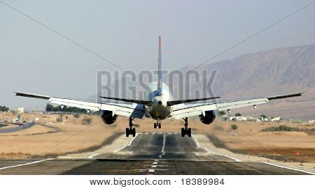 Passenger airplane landing on runway in airport of Eilat, Israel.
