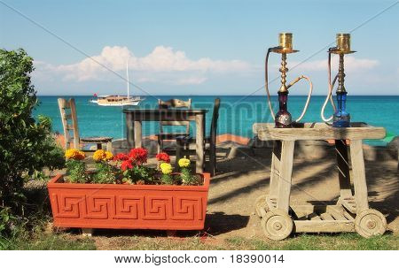 Two traditional turkish waterpipes (nargile) on the table in outdoor restaurant with view on Mediterranean sea in Kemer, Turkey.