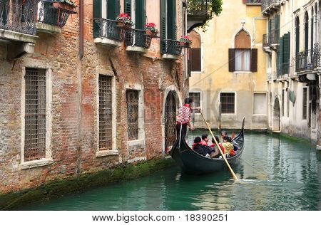 Venetian canal and gondola among old houses in Venice, Italy.