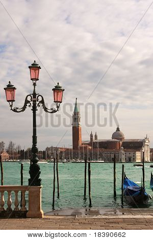 Vertical oriented photo of venetian lamppost, gondola on Grand Canal and San Giorgio Maggiore church in Venice, Italy.