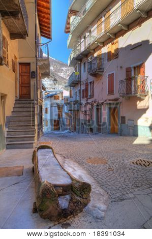 Vertical oriented image of small street among colorful houses in Limone Piemonte town in northern Italy.