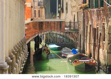 Gondola passing on small canal among old historic houses and bridge in Venice, Italy.