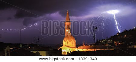 Panoramic view on lightning over Alba and surrounding hills during thunderstorm in northern Italy.