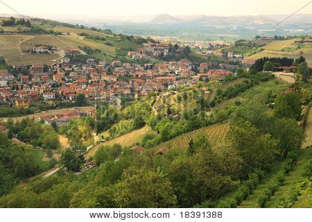 Vista aérea en pequeña ciudad entre verdes colinas en Piamonte, norte de Italia.