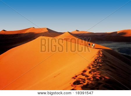 people hiking on beautiful orange namibian sand dunes