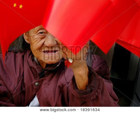 Chinese old woman selling touristic flags on Tiananmen square Beijing