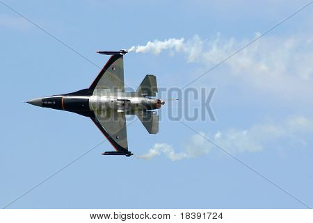 f16 flying with smoke clouds on clear blue sky