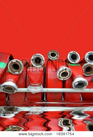 red rolls of fire hoses on red background