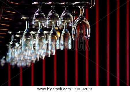 cuelga copas de vinos y champán en un bar con fondo oscuro