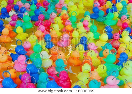 background of colorful plastic toy ducklings floating on a fair