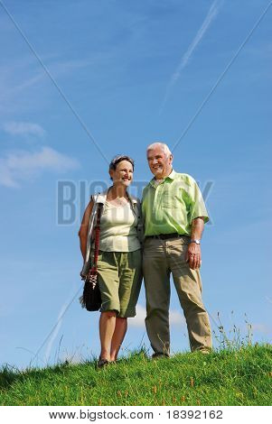 senior retired smiling couple walking outdoors on green grass hill with blue sky background