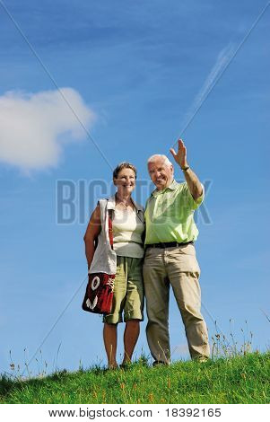 senior retired smiling couple, man greeting with his hand, walking outdoors on green grass hill with blue sky background