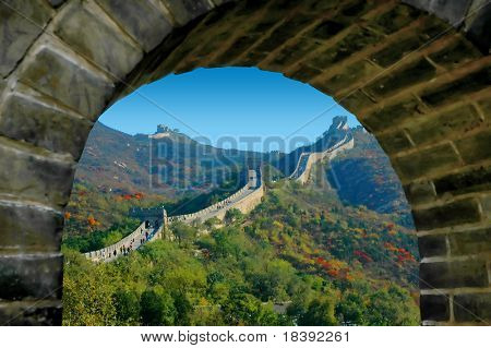 chinese wall in autumn, seen through a brick stone window