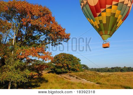hot air balloon flying over autumn landscape