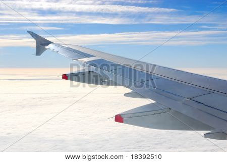 wing of passengerplane flying above the clouds