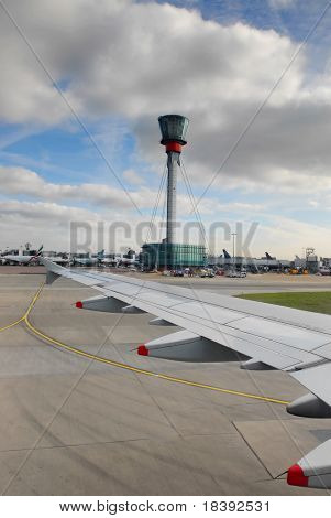 view on wing and control tower after landing at heathrow airport, london, UK