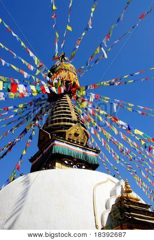 nepalese stupa with buddha eyes and prayer flags with clear blue sky