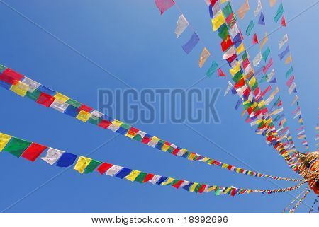 colorul prayer flags on bodhnath stupa in kathmandu, nepal, with clear blue sky