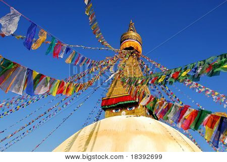 bodhnath stupa in kathmandu with buddha eyes and prayer flags with clear blue sky
