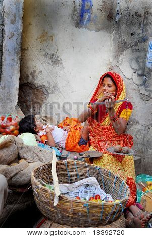 colorful woman on market in india with pair of scales