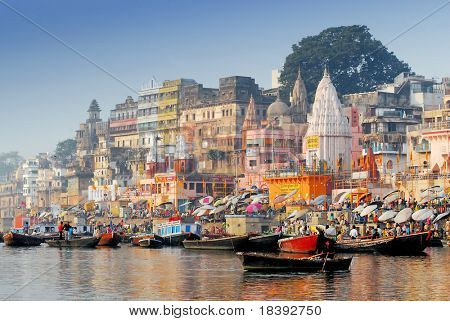 boats and reflection in water at the main ghat in varanasi on a sunny day