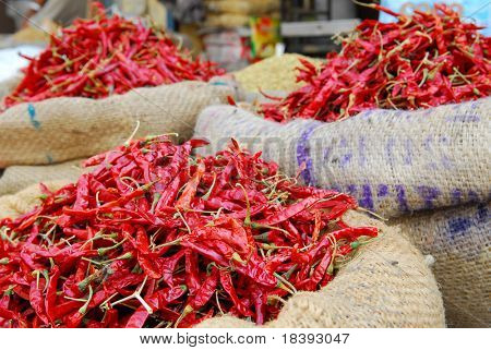jute gunny bags filled with red hot chili peppers on indian market