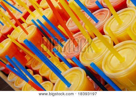 Plastic cups filled with fresh fruit juice and straws