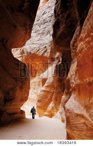 Tourist walking in Siq of world wonder Petra in Jordan