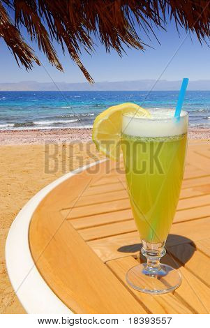 Glass with fresh lemon mint juice on wooden table on the beach with view on blue sea from under palm leaves umbrella