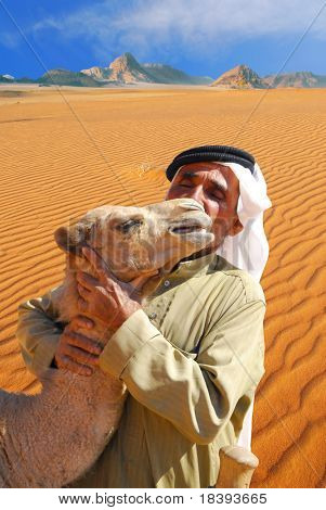 Traditional arab man kissing and hugging a baby camel in Wadi Rum desert, Jordan