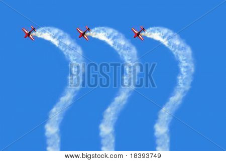 Aerobatic team flying question marks in the blue sky with white smoke