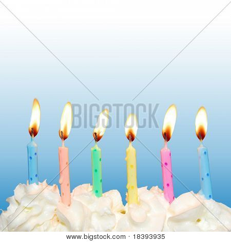 Colorful birthday candles on cake with whipped cream and blue square background