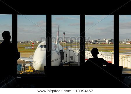 silhouettes of people waiting at the airport for their flight