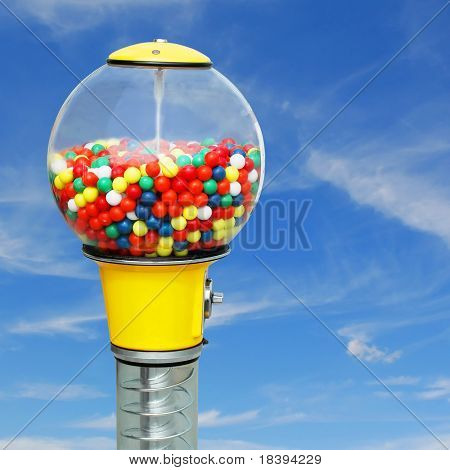 Gumball machine with colorful chewing gum balls on square blue sky background