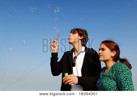 Concept: stay young! Man in his twenties blowing soap bubbles for his girlfriend on blue sky background